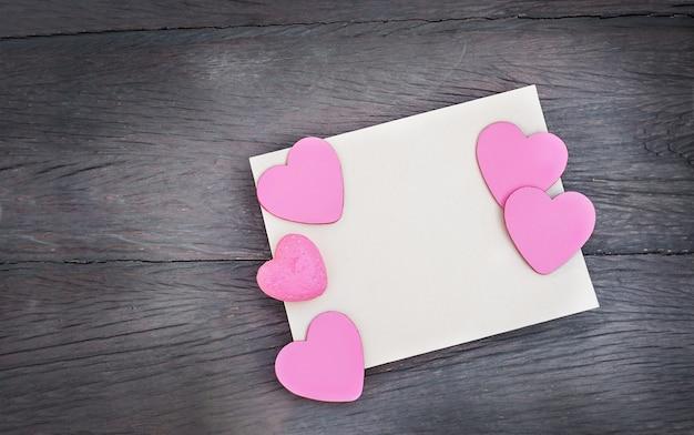 Corações em um cartão postal com espaço de cópia em um fundo de madeira. uma folha de papel com corações rosa em um fundo escuro de madeira