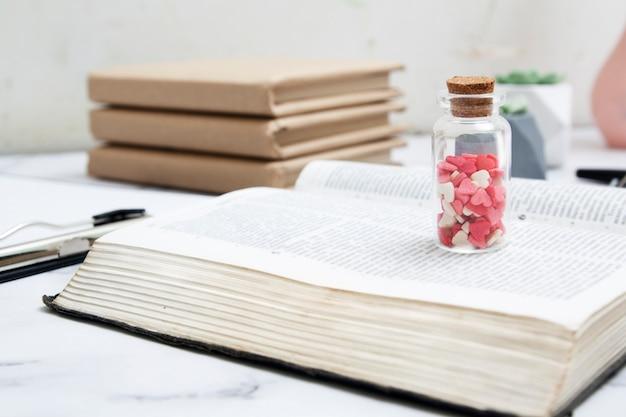 Corações em uma garrafa de vidro em uma bíblia aberta. bíblia como fonte do conceito de amor