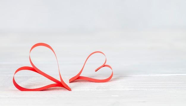 Corações feitos à mão de papel vermelho sobre fundo azul, vista superior, espaço de cópia