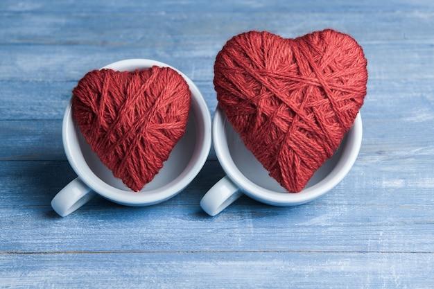 Corações feitos à mão em xícaras de café. manhã dos namorados