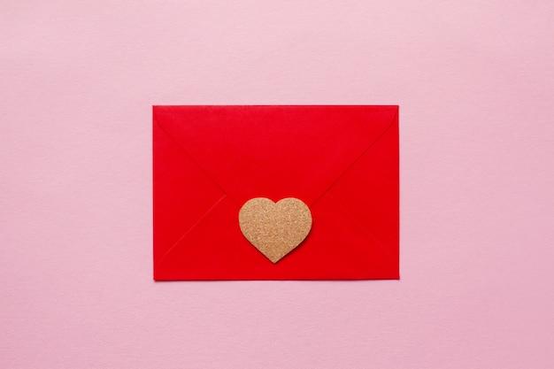 Corações lindas de madeira em um envelope de papel vermelho amam mensagem