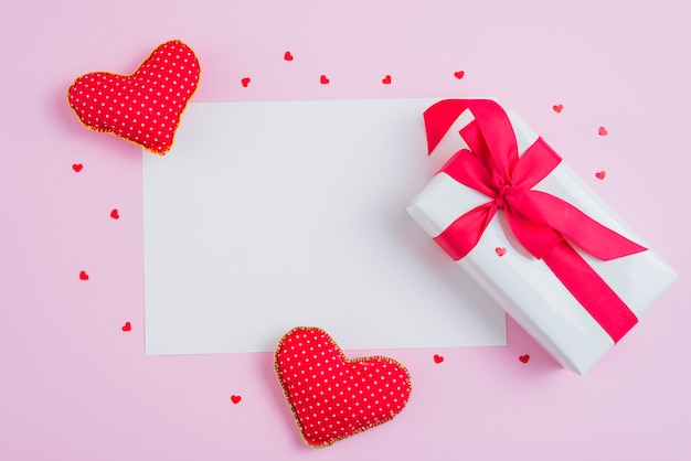 Corações moles e presente adorável perto de papel