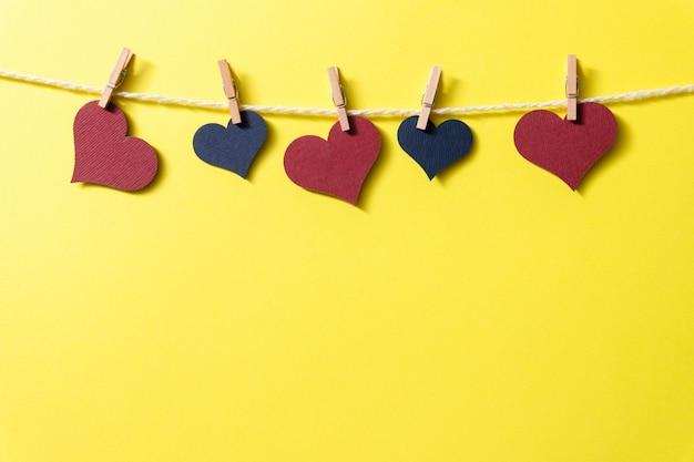 Corações multicoloridos com uma corda em pequenos prendedores de roupa penduram em um fundo amarelo.
