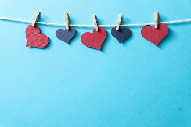 Corações multicoloridos com uma corda em pequenos prendedores de roupa penduram em um fundo azul.