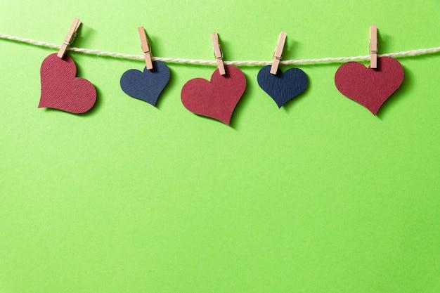 Corações multicoloridos com uma corda em pequenos prendedores de roupa penduram em um fundo verde.