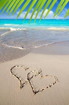 Corações no amor escrito na areia da praia do caribe