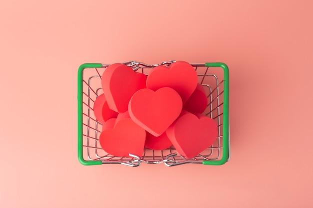 Corações no carrinho de compras e no carrinho de supermercado contra um fundo colorido. plano de fundo para o dia dos namorados (14 de fevereiro) e o amor.