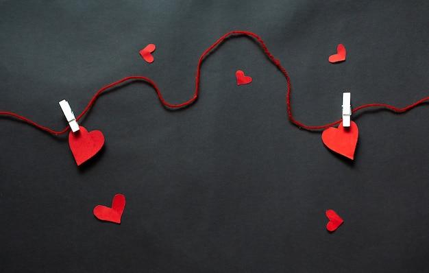 Corações pendurados na corda em um fundo preto. plano de fundo dia dos namorados