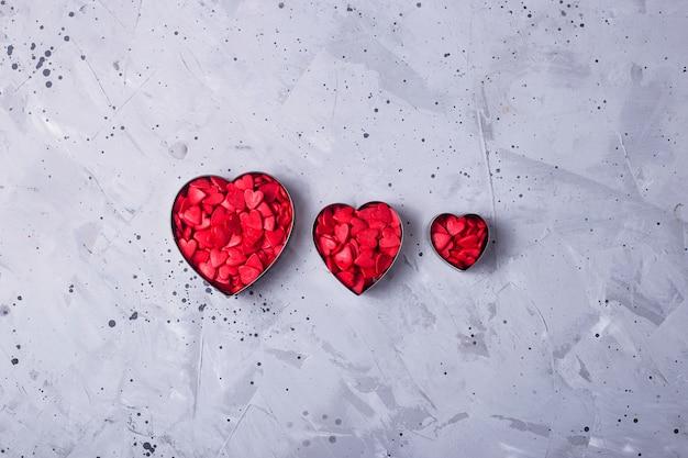 Corações pequenas vermelhas sobre uma mesa cinza como um símbolo de amor no dia dos namorados