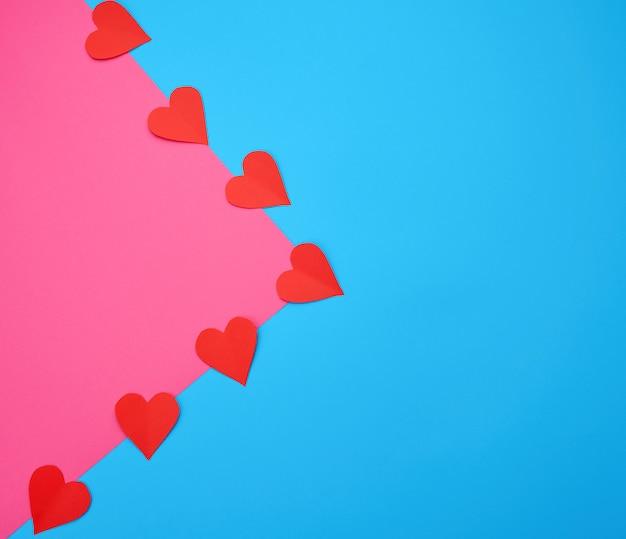 Corações recortadas em papel vermelho sobre um fundo azul e rosa