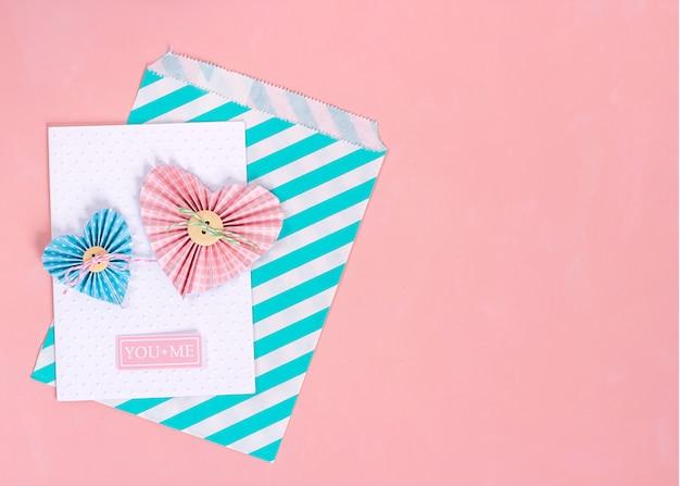 Corações scrapbooking do papel do whith do cartão do dia de valentim no fundo cor-de-rosa.