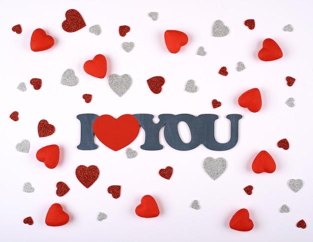 Corações vermelhas e prata sobre um fundo branco em torno da inscrição eu te amo. dia dos namorados.