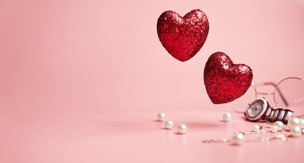 Corações vermelhos brilhantes, conceito de moda do dia dos namorados, sobre fundo rosa, cópia espaço, banner. foto de alta qualidade