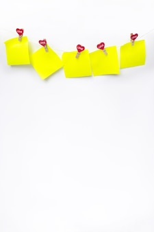 Corações vermelhos com notas em branco na corda com prendedores de roupa, sobre um fundo branco. lugar para texto