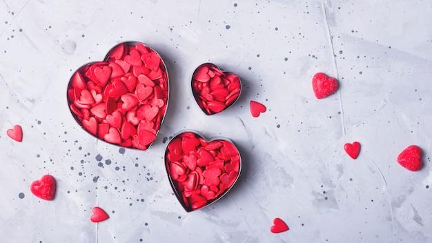 Corações vermelhos como um símbolo do dia dos namorados em pó de confeitaria em um fundo cinza e concreto.