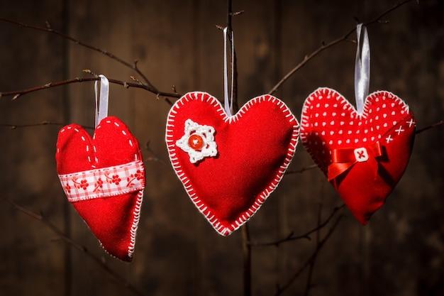 Corações vermelhos costurados à mão em fundo de madeira