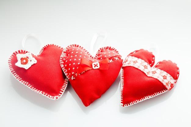 Corações vermelhos costurados à mão em um fundo branco