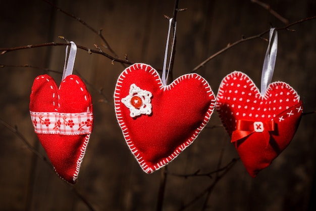 Corações vermelhos costurados feitos à mão pendurados em um galho. decorações do dia das mães