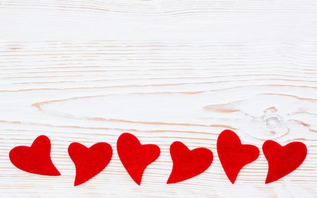 Corações vermelhos de feltro em um branco de madeira