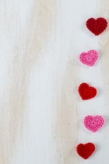 Corações vermelhos de malha em um fundo branco de madeira