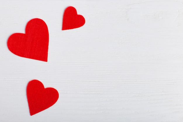 Corações vermelhos de tamanhos diferentes em um fundo branco