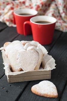 Corações vermelhos do copo e do biscoito em uma superfície preta