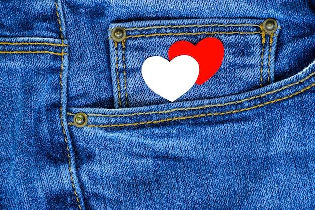 Corações vermelhos e brancos no bolso da calça jeans. plano de fundo para o dia dos namorados.