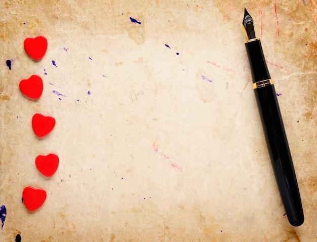Corações vermelhos e caneta-tinteiro em papel velho