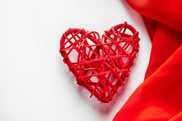 Corações vermelhos e fita de seda em um fundo branco.