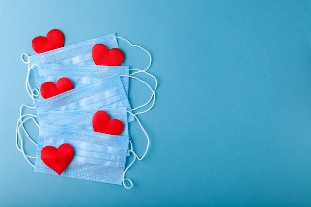 Corações vermelhos e máscara de proteção médica azul anti-epidêmica