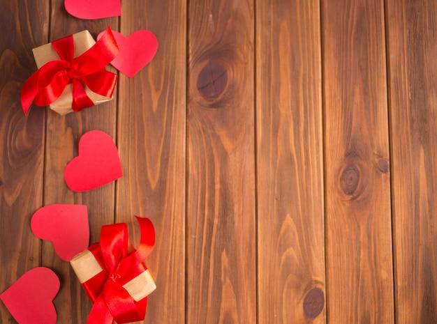 Corações vermelhos e presentes em um fundo de madeira. presente de dia dos namorados