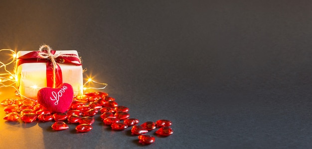 Corações vermelhos e uma caixa de presente em um fundo preto - feriado do dia dos namorados