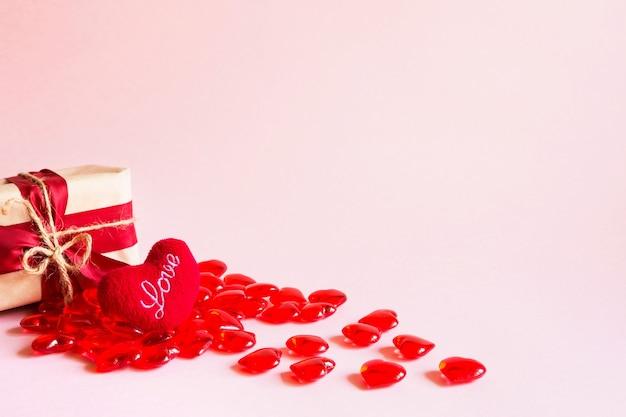 Corações vermelhos e uma caixa de presente em um fundo rosa - feriado do dia dos namorados