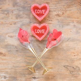 Corações vermelhos em copos na mesa de madeira