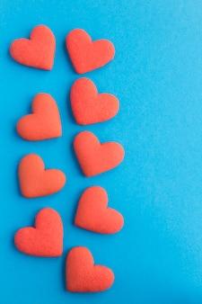 Corações vermelhos em forma de cookies na superfície azul. copie o espaço. vista do topo. localização vertical.