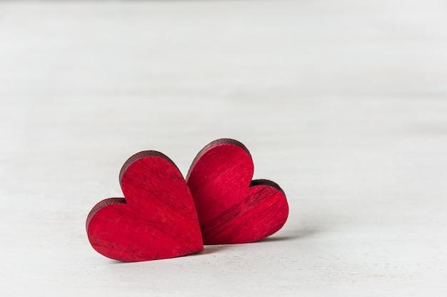 Corações vermelhos em fundo branco de madeira. cartão de saudação conceito de dia dos namorados.