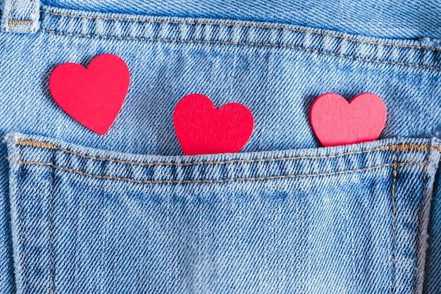 Corações vermelhos em fundo de jeans velho