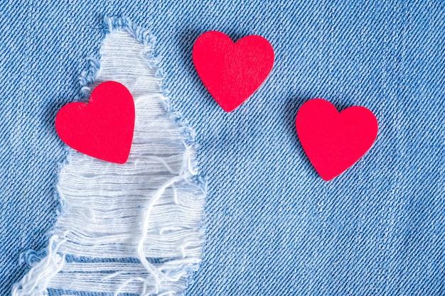Corações vermelhos em fundo de jeans