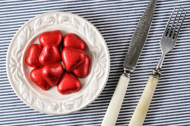 Corações vermelhos em um prato e uma faca com um garfo