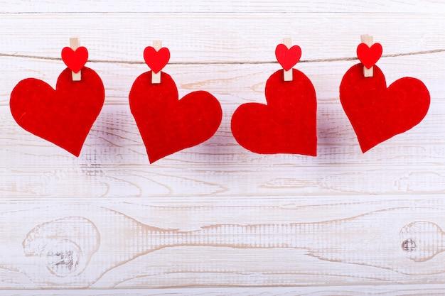 Corações vermelhos em uma corda com prendedores de roupa, sobre um fundo branco de madeira. lugar para texto, copie o espaço.
