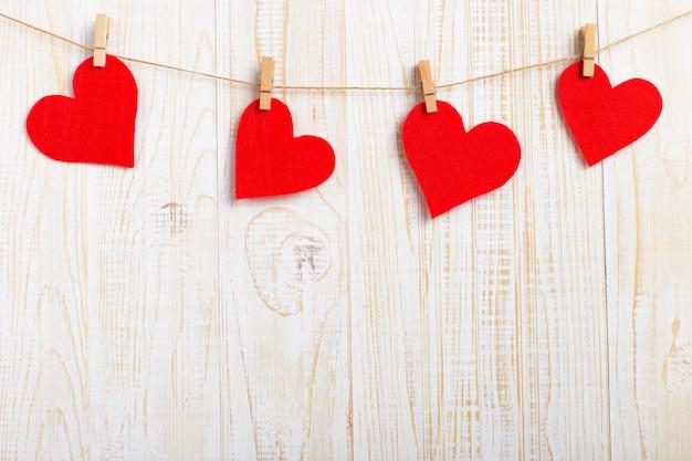 Corações vermelhos em uma corda com prendedores de roupa, sobre um fundo branco de madeira