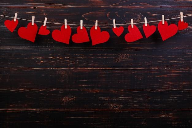 Corações vermelhos em uma corda com prendedores de roupa, sobre um fundo preto de madeira. lugar para texto, copie o espaço.