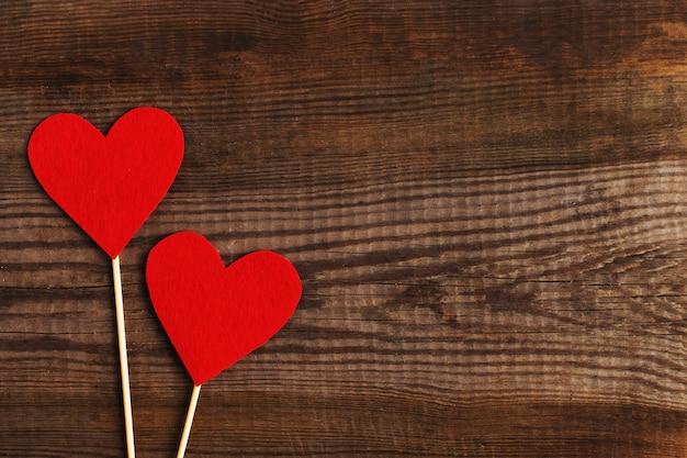Corações vermelhos em uma mesa de madeira.