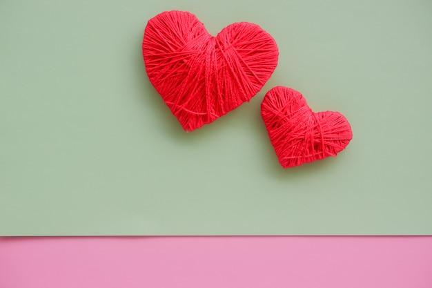 Corações vermelhos mentem na parede pastel. o conceito de dia dos namorados, família, casal feliz. dois corações feitos de fios. cartão de dia dos namorados. amor, romance e conceito de família