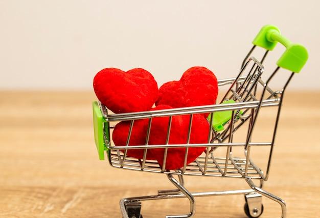 Corações vermelhos no carrinho do supermercado cheio de amor e cheio de doce momento para casal