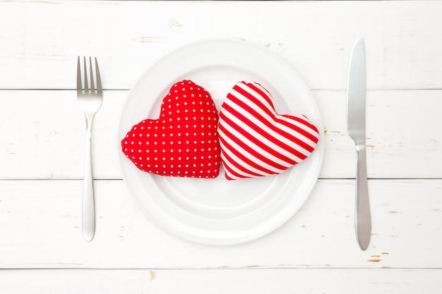 Corações vermelhos no prato, garfo e faca em fundo de madeira