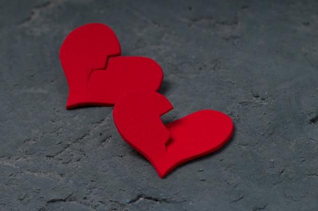 Corações vermelhos rachados no muro de concreto. conceito de coração partido