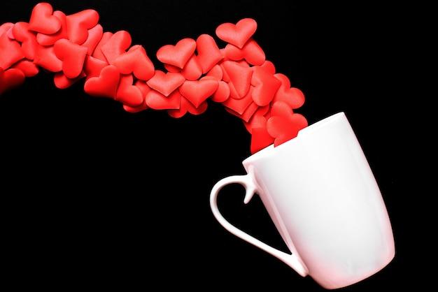 Corações vermelhos saem de um copo branco cheio de amor, isolado no fundo preto.