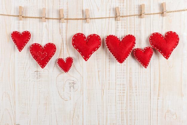 Corações vermelhos são guardados por prendedores de roupa na corda da juta, em madeira branca. copie o espaço