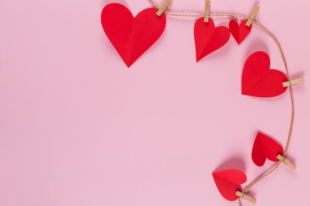 Corações vermelhos são mantidos por prendedores de roupa na corda de juta, em fundo rosa. copie o espaço.